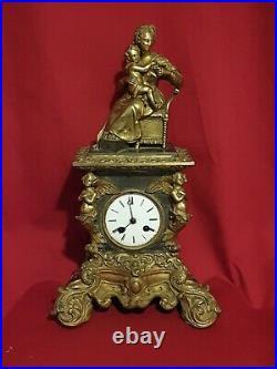 Pendule en bronze, sujet figurant une femme et son enfant, montant angelots