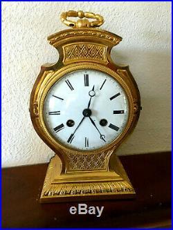Pendule tête de poupée XIXeme en bronze doré. Réveil et sonnerie au passage